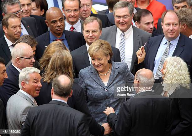 German Chancellor Angela Merkel casts her vote on a third bailout package for economicallytroubled Eurozone member Greece as she attends a meeting of...
