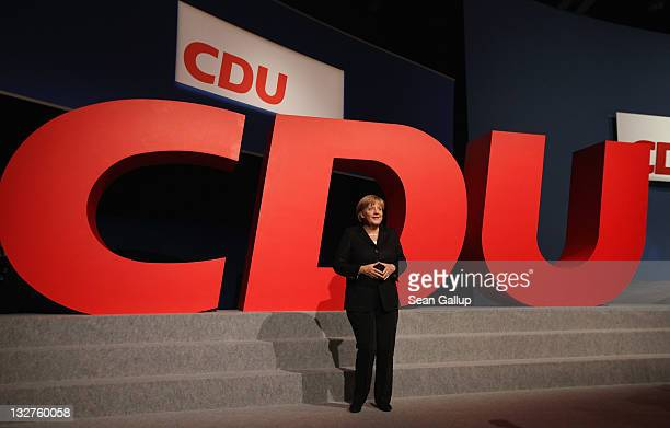 German Chancellor Angela Merkel, Chairwoman of the German Christian Democrats , walks by a giant logo of the CDU at the 24th CDU Party Congress on...