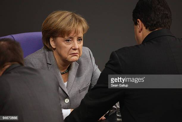 German Chancellor Angela Merkel chats with colleagues prior to giving a government declaration on the Copenhagen climate summit at the Reichstag the...