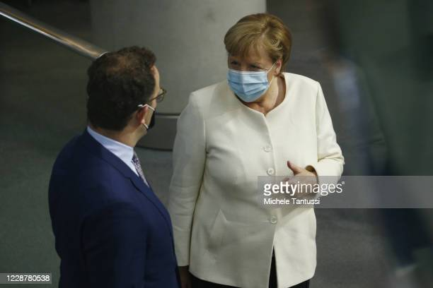 German Chancellor Angela Merkel chats with Health Minister Jens Spahn as they arrive at the plenary room of the germans lower house of Parliament or...