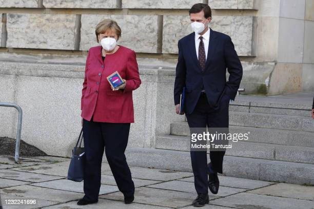 German Chancellor Angela Merkel chats with her spokesman and Chief of the Chancellery Press Office Steffen Seibert as she leaves after a meeting of...