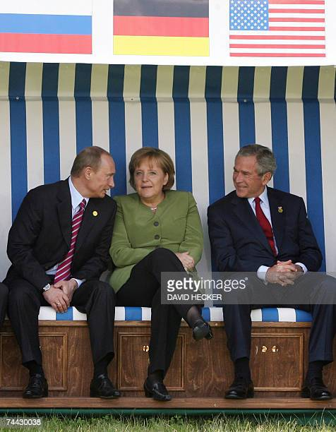 German Chancellor Angela Merkel chats with Russian President Vladimir Putin and US President George W Bush as they pose in a giant beach chair for a...