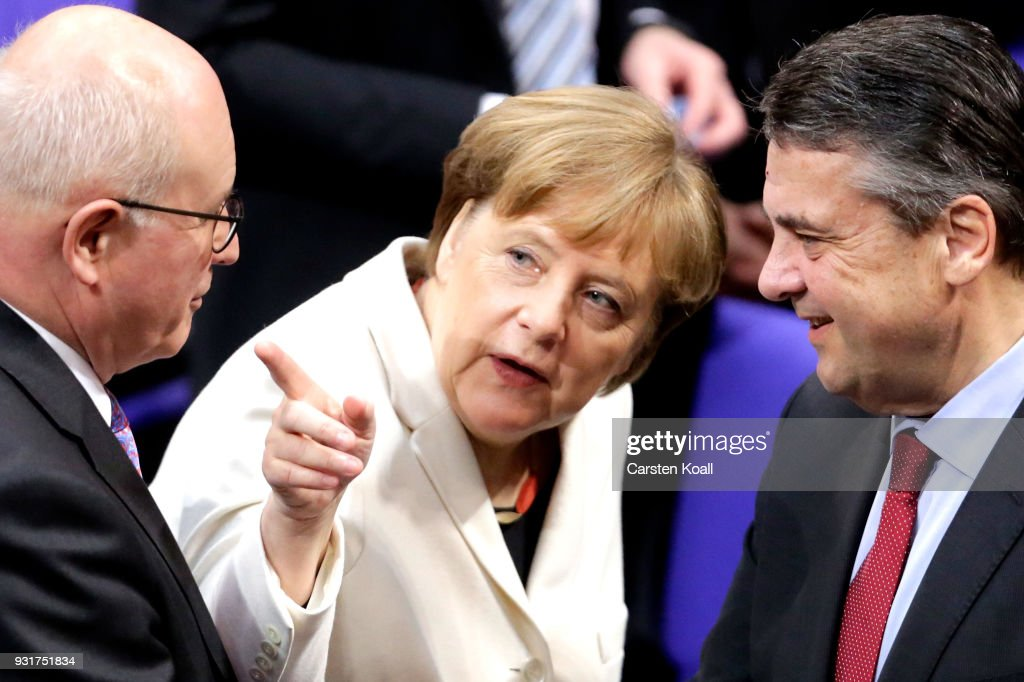 German Chancellor Angela Merkel (C) chats with Social Democrat (SPD) and outgoing Foreign Minister Sigmar Gabriel (R) and Christian Democrat (CDU) Volker Kauder during Merkel's election by the Bundestag for a fourth term as chancellor on March 14, 2018 in Berlin, Germany. Members of the new German government, a coalition between Christian Democrats (CDU/CSU) and Social Democrats (SPD), will be sworn in today and will begin work immediately. The new government took the longest to create of any government in modern German history following elections last September that left the German Christian Democrats (CDU) as the strongest party but with too few votes in order to have a strong hand in determining the next coalition.