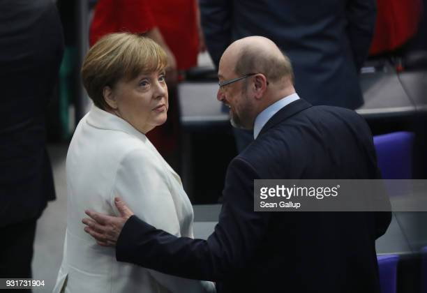 German Chancellor Angela Merkel chats with Social Democrat Martin Schulz who ran against her in elections last year during Merkel's election by the...