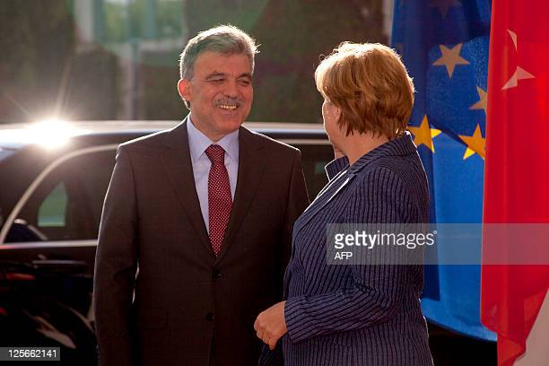 German Chancellor Angela Merkel chats with Turkey's President Abdullah Gul as he arrives for their meeting at the Chancellery in Berlin on September...