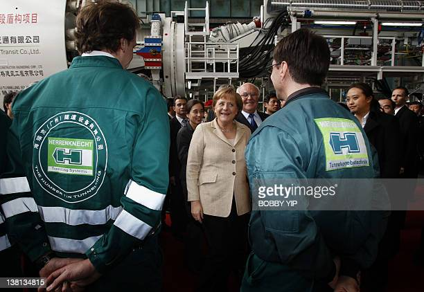 German Chancellor Angela Merkel chats with workers during her visit to a plant of Herrenknecht Tunnelling Equipment Co Ltd in Guangzhou on February 3...