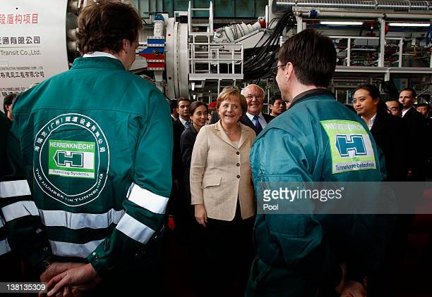 German Chancellor Angela Merkel chats with workers during her visit to a plant of Herrenknecht Tunnelling Equipment Co Ltd on February 3 2012 in...