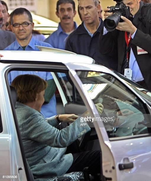 German Chancellor Angela Merkel checks a car during her visit to the VW plant on May 15 in Sao Bernardo do Campo southern Sao Paulo Brazil Merkel is...