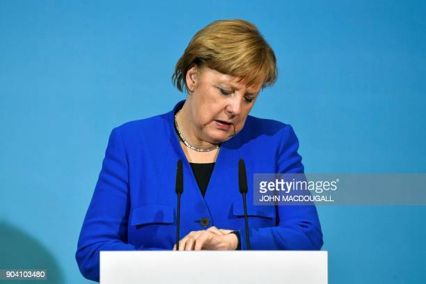 German Chancellor Angela Merkel checks the time during a joint press conference with the leader of the Social Democratic Party and the leader of the...