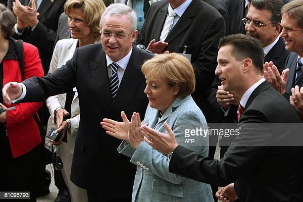 German Chancellor Angela Merkel claps her hands next to Volkswagen' s CEO Martin Winterkorn and the president for Volkswagen in Brazil Thomas Schmall...