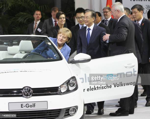 German Chancellor Angela Merkel climbs into a Volswagen EOS electric car as Chinese Premier Wen Jiabao and Volkswagen CEO Martin Winterkorn look on...