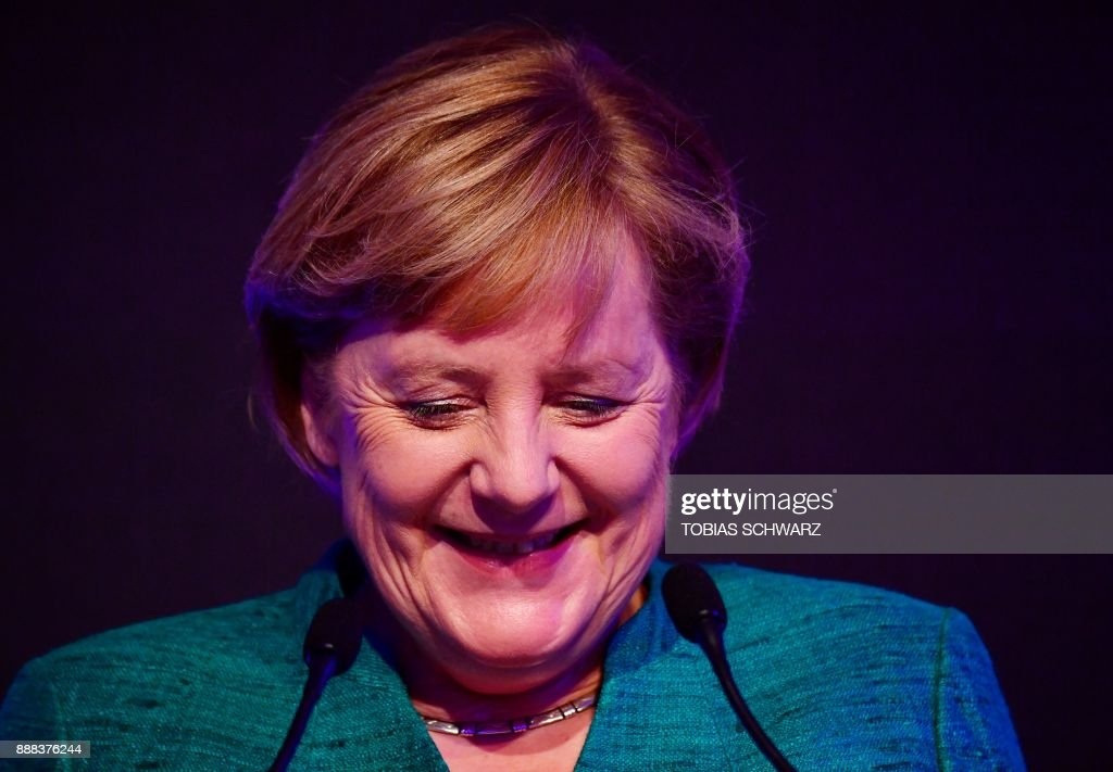 German Chancellor Angela Merkel delivers a speech during the inauguration ceremony of a special ICE high speed train at the railway station in Berlin, as the train inaugurates a new fast route between Munich and Berlin on December 8, 2017. According to Deutsche Bahn, ICE high speed trains will be able to cover the stretch between Munich and the German capital Berlin in less than four hours. / AFP PHOTO / Tobias SCHWARZ