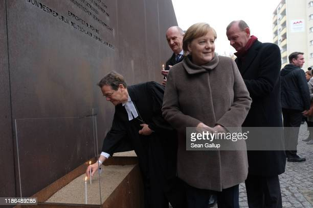 German Chancellor Angela Merkel departs after placing a candle at a memorial to the Berlin Wall at Bernauer Strasse following a ceremony to celebrate...