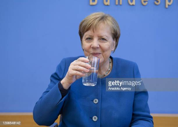 German Chancellor Angela Merkel drinks a glass of water after a press conference on precautions taken against coronavirus at Federal Press Conference...