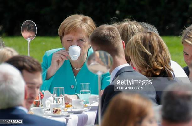"German Chancellor Angela Merkel drinks coffee as she attends a ""coffee table"" event hosted by the German President to celebrate the 70th anniversary..."