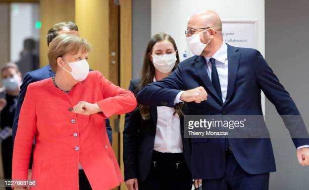 German Chancellor Angela Merkel elbow bumps the President of the European Council Charles Michel during an EU summit on July 17 2020 in Brussels...