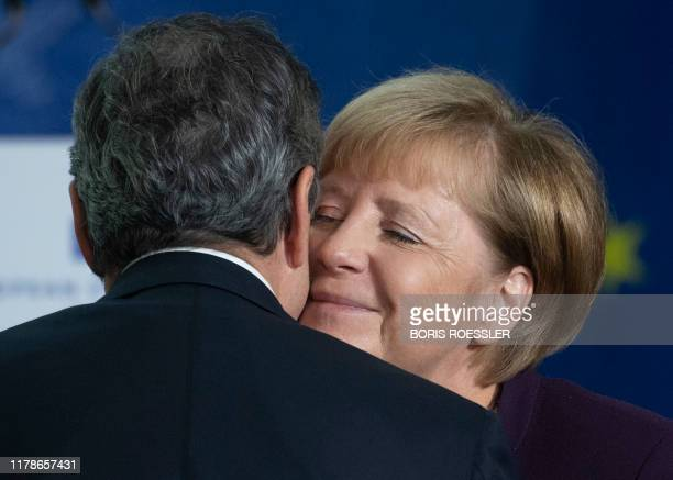 German Chancellor Angela Merkel embraces Mario Draghi outgoing President of the European Central Bank at a handing over ceremony to his successor...