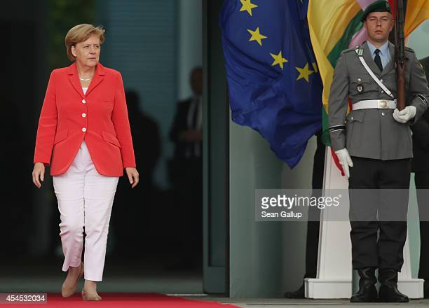 German Chancellor Angela Merkel emerges at the Chancellery to welcome Myanmar President Thein Sein on September 3, 2014 in Berlin, Germany. President...