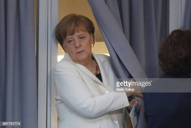 German Chancellor Angela Merkel emerges from filling out her ballot during her election by the Bundestag for a fourth term as chancellor on March 14...