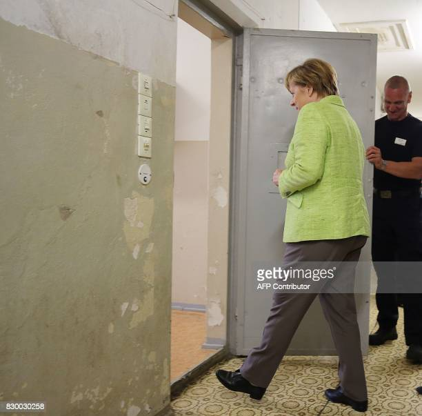 German Chancellor Angela Merkel enters a cell as she visits the BerlinHohenschönhausen Memorial at the site of a former prison of the East German...