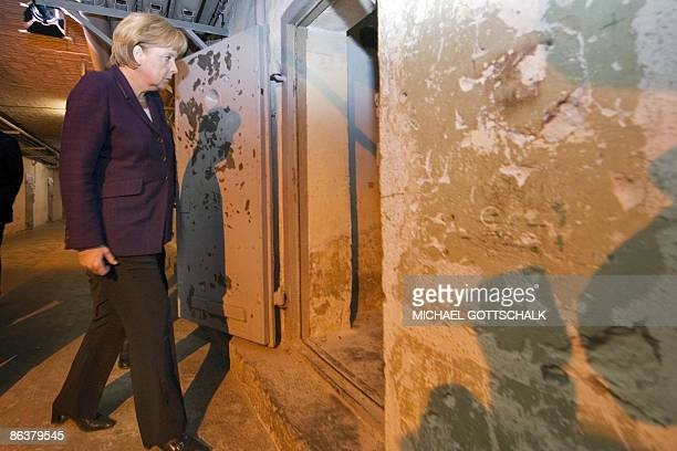German Chancellor Angela Merkel enters a prison cell as she visits the memorial site at the former Stasi East German secret police in Berlin's...