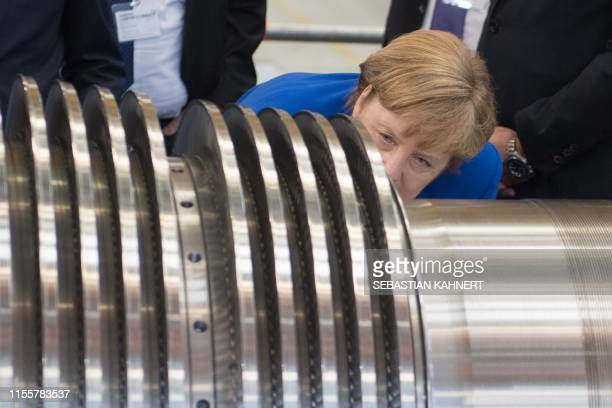 German Chancellor Angela Merkel examines a turbine at the Siemens plant in Goerlitz, eastern Germany, one and a half months before the state...