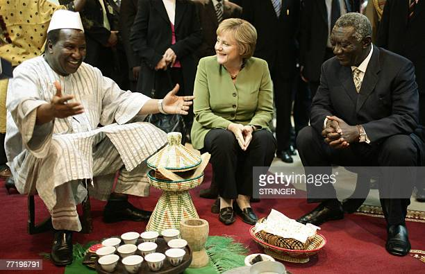 German Chancellor Angela Merkel exchanges gifts with Ghana's President and African Union President John Kutuor and Chairman of the African Commission...