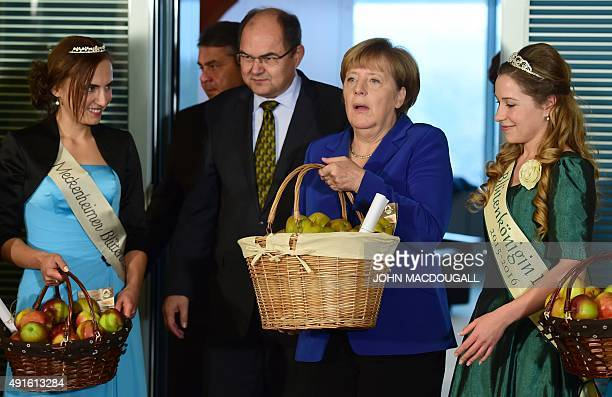 German Chancellor Angela Merkel feels the weight of an apple basket as German Vice Chancellor Economy and Energy Minister Sigmar Gabriel and German...