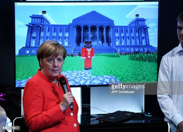German Chancellor Angela Merkel follows a presentation of Microsoft´s Minecraft game at the stand of Microsoft during the gaming fair 'gamescom' in...