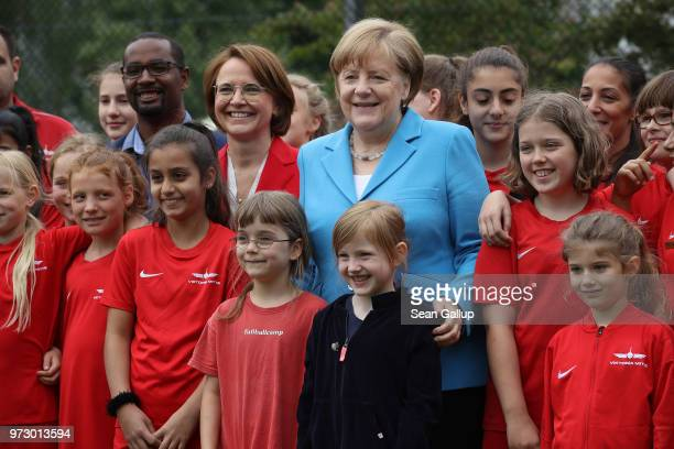 German Chancellor Angela Merkel former football star Cacau and Federal Commissioner for Migration Refugees and Integration Annette WidmannMauz pose...