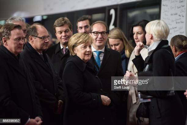 German Chancellor Angela Merkel former German Transport and Digital Technologies Minister Alexander Dobrindt and other guests stand in front of an...