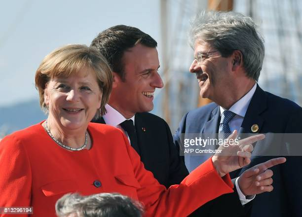 German Chancellor Angela Merkel French President Emmanuel Macron and Italy's Prime Minister Paolo Gentiloni share a light moment as they wait for the...