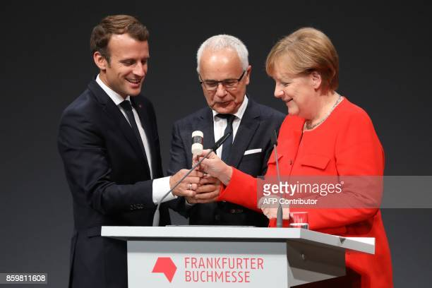 German Chancellor Angela Merkel French President Emmanuel Macron and president of the German Publishers and Booksellers Association Heinrich...