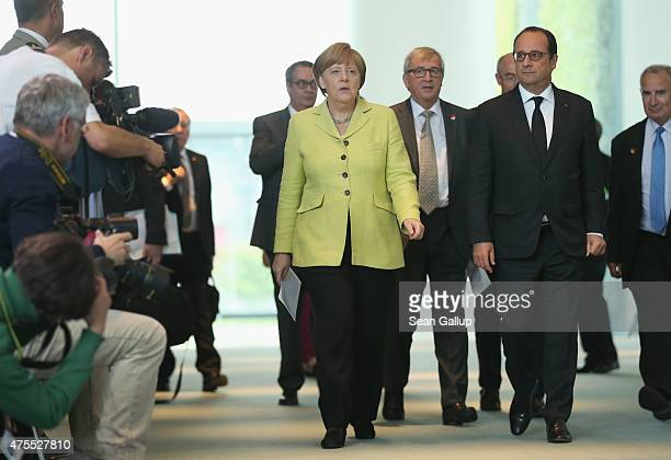 German Chancellor Angela Merkel, French President Francois Hollande and European Union Commission President Jean-Claude Juncker arrive to give...