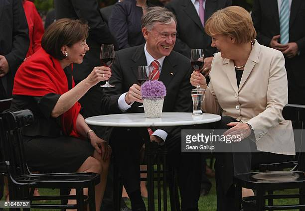 German Chancellor Angela Merkel German President Horst Koehler and his wife Eva Luise Koehler chat over glasses of red wine at the annual summer...