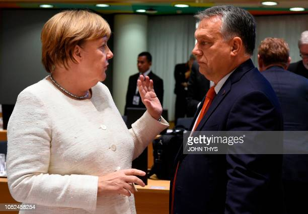 German Chancellor Angela Merkel gestures as she speaks with Hungary's Prime Minister Viktor Orban as they arrive for an Asia Europe Meeting at the...