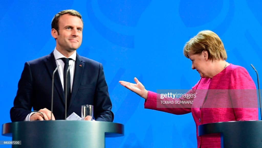 TOPSHOT - German Chancellor Angela Merkel gestures to French President Emmanuel Macron after addressing a press conference at the chancellery in Berlin on May 15, 2017, a day after the new French president took office. Emmanuel Macron is on his first trip abroad as French president. / AFP PHOTO / Tobias SCHWARZ