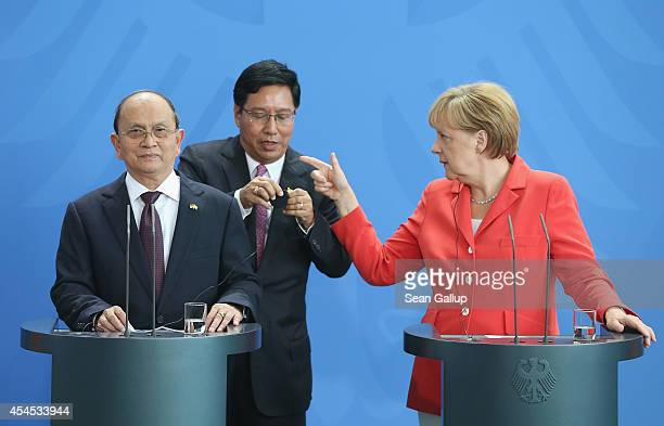 German Chancellor Angela Merkel gestures while an aide assists Myanmar President Thein Sein with his headphone prior to speaking to the media...