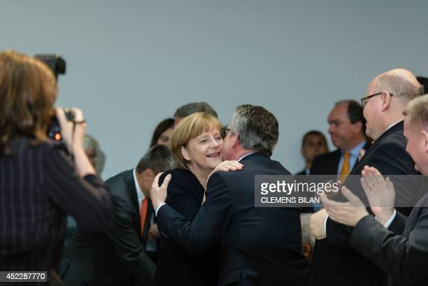 German Chancellor Angela Merkel gets hugged by German Interior Minister Thomas de Maiziere during a festive event to celebrate Merkel's 60th...