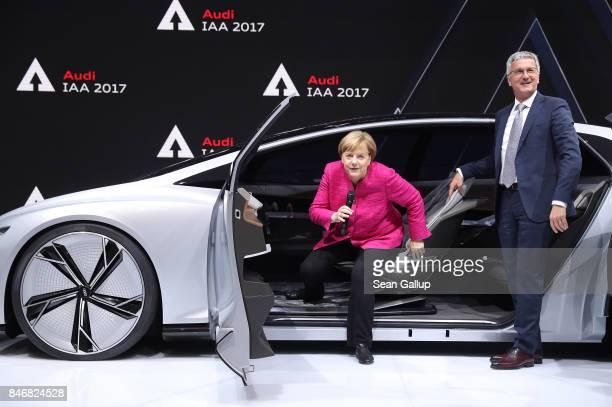 German Chancellor Angela Merkel gets out of an Audi Aicon autonomous electric concept car as Rupert Stadler Chairman of German carmaker Audi looks on...