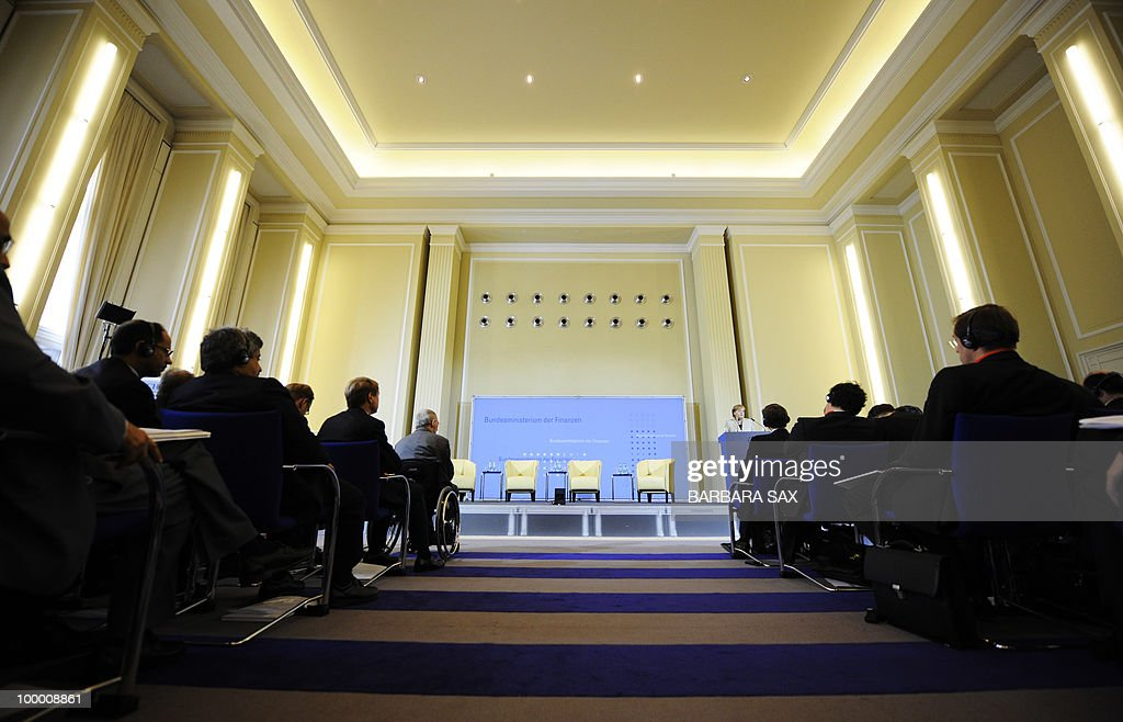 German Chancellor Angela Merkel (back R) gives a speech as Finance Minister Wolfgang Schaeuble (L) and conference participants listen during a conference on financial regulation on May 20, 2010 at the Finance Ministry in Berlin. Merkel said she would lead a campaign for a tax on financial markets at the next meeting of the Group of 20 developed economies in June 2010 and called for international support.