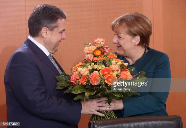German Chancellor Angela Merkel gives flowers to Vice Chancellor and Foreign Minister Sigmar Gabriel in celebration of the birth of his baby daughter...