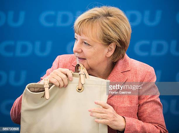 German Chancellor Angela Merkel grabs her bag before the party board meeting of the Christian Democratic Union Party CDU on August 15, 2016 in...
