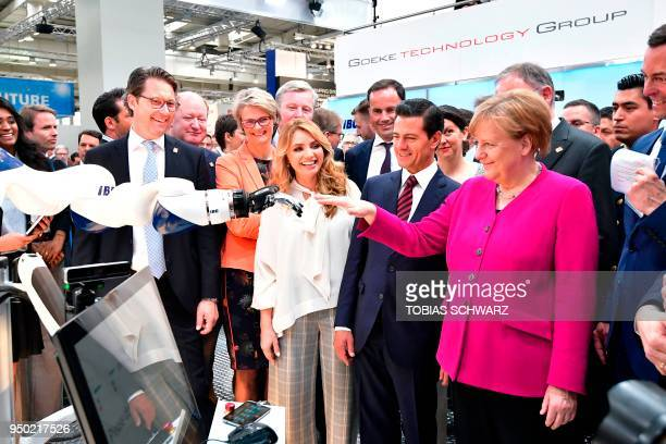German Chancellor Angela Merkel greets a robot next to Mexican President Enrique Pena Nieto his wife Angelica Rivera German Minister of Education and...