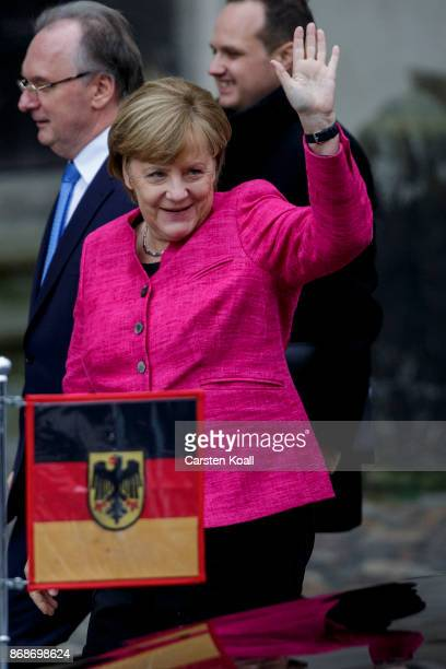 German Chancellor Angela Merkel greets as she arrives together with SaxonyAnhalt's State Premier Reiner Haseloff for a service in Schlosskirche...