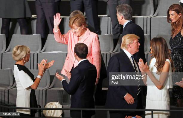 German Chancellor Angela Merkel greets as she attends a concert with French President Emmanuel Macron his wife Brigitte Macron US President Donald...