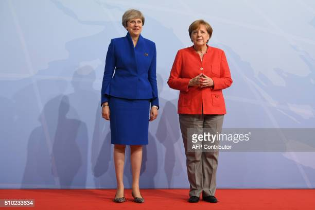German Chancellor Angela Merkel greets Britain's Prime Minister Theresa May prior to the start of the first working session of the G20 meeting in...