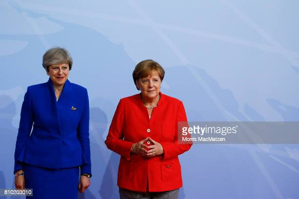 German Chancellor Angela Merkel greets British Prime Minister Theresa May upon her arrival for the first day of the G20 economic summit on July 7...