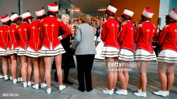 German Chancellor Angela Merkel greets carnival dancers as she receives royal couples of the federal German states during the traditional carnival...