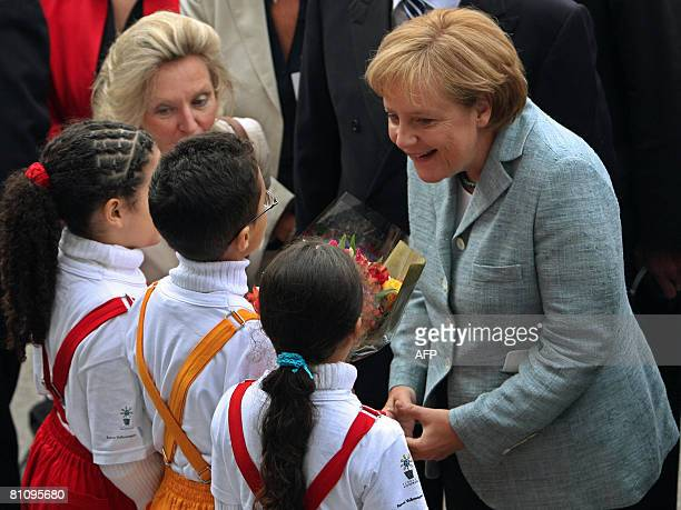 German Chancellor Angela Merkel greets children during a visit to the Volkswagen plant on May 15 in Sao Bernardo do Campo southern Sao Paulo Brazil...